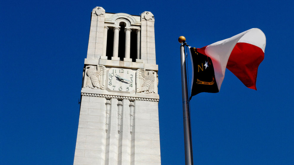 Photo of NC State Memorial Belltower behind flag of North Carolina.