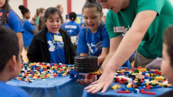 Photo of NC State Goodnight Scholar Sid Rogers teaching elementary school kids about physics using LEGO.