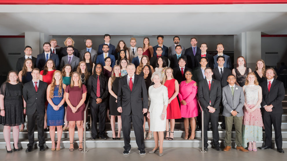 Group photo of NC State Goodnight Scholars class of 2019 and Dr. Jim and Mrs. Ann Goodnight at the Goodnight Graduation Gala on April 2019 in Reynolds Coliseum.