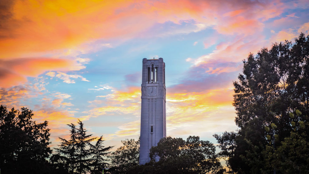 Photo of NC State Memorial Belltower with sunset backdrop.