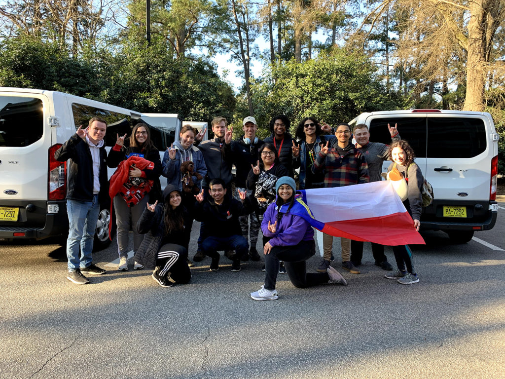 Group photograph of NC State Goodnight Scholars holding North Carolina flag and preparing to leave for Mountains to Coast service trip.