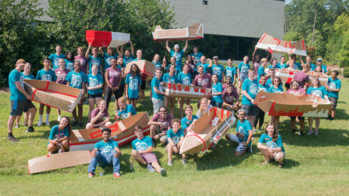 Group photo of the Goodnight Scholars class of 2023 holding their cardboard boats during the summer retreat at SAS Institute in Cary, North Carolina.