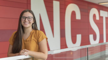 Goodnight Scholar Lacey Malinsky '22 standing in front of the NC State mural inside Talley Student Union.